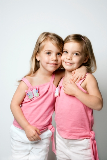 Girl child twin sisters embracing.